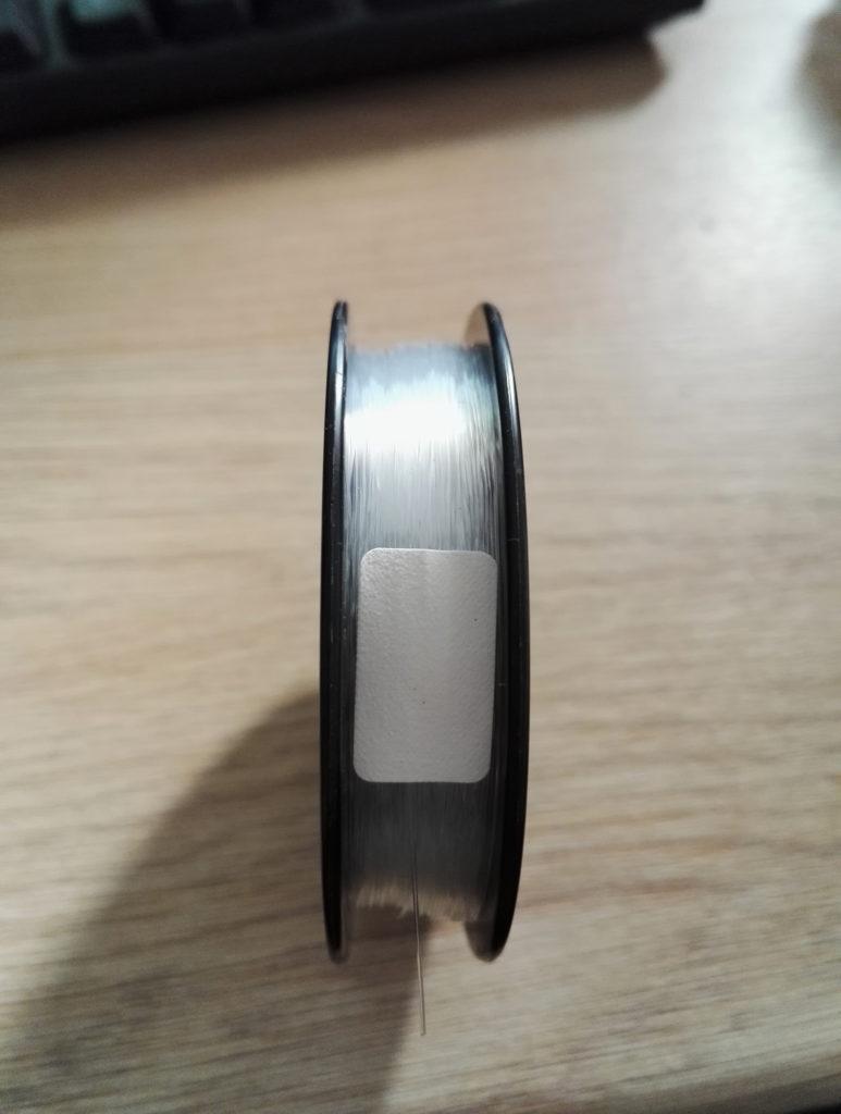 Détail du rangement du fil et de la pastille de blocage sur une bobine neuve